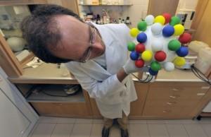 Dr inż. Rafał Szmigielski z Instytutu Chemii Fizycznej Polskiej   Akademii Nauk (IChF PAN) w Warszawie prezentuje poglądowy model drobiny   pyłu zawieszonego. (Źródło: IChF PAN, Grzegorz Krzyżewski)