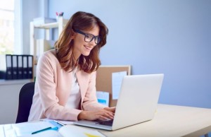 Happy woman working on her laptop from home office